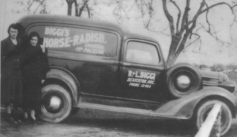 "Rose Biggi and family member standing next to car reading ""Biggi's Horse-Radish"""