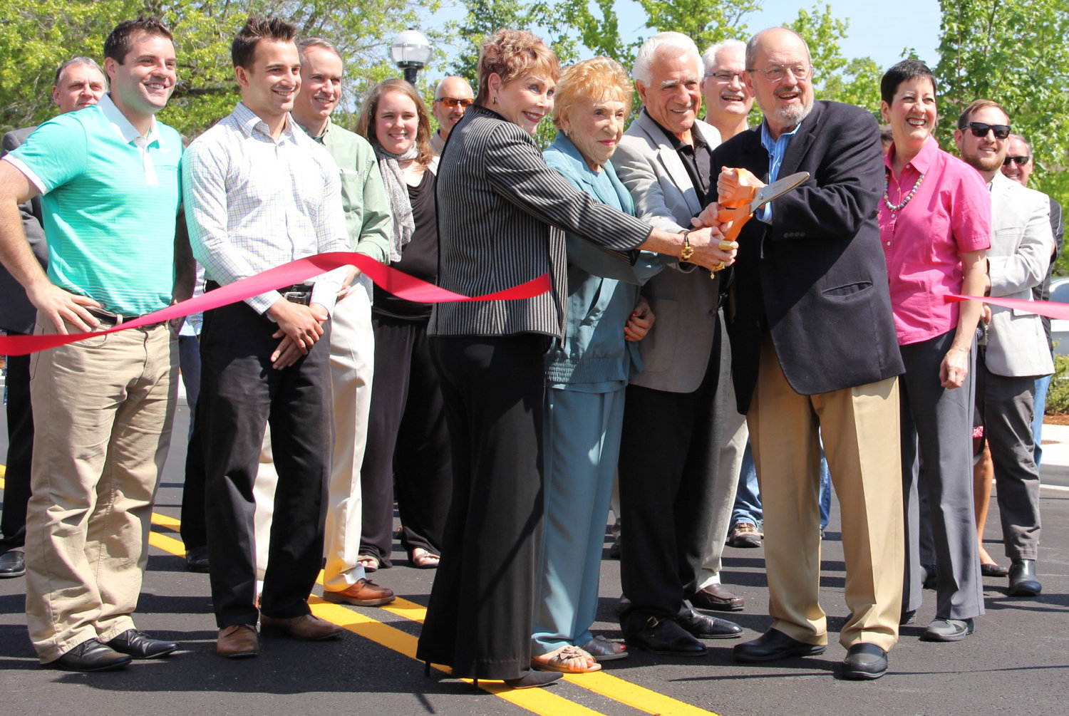 Geno Biggi, family, and guests cutting the ribbon to open Rose Biggi Avenue