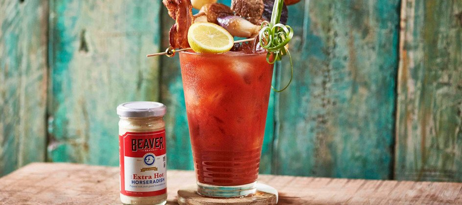 Iced bloody mary topped with lemon, bacon, steak, and onions, plus Beaver Brand Extra Hot Horseradish